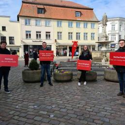 Vier SPD-Unterstuetzer präsentieren Schilder in Güstrow auf dem Pferdemarkt