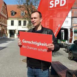 Johannes Arlt hält ein Schild mit seinen Kernforderungen hoch